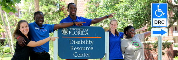 "Students standing by the road sign of ""University of Florida, Disability Resource Center"" and pointing to the right, showing the direction to Disability Resource Center (DRC) at University of Florida"